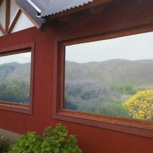 Cerro Napostá reflejado en los ventanales espejados