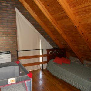 amplio dormitorio que abarca toda la planta alta con una cama de dos plazas, otra de un aplaza y cuna para bebé